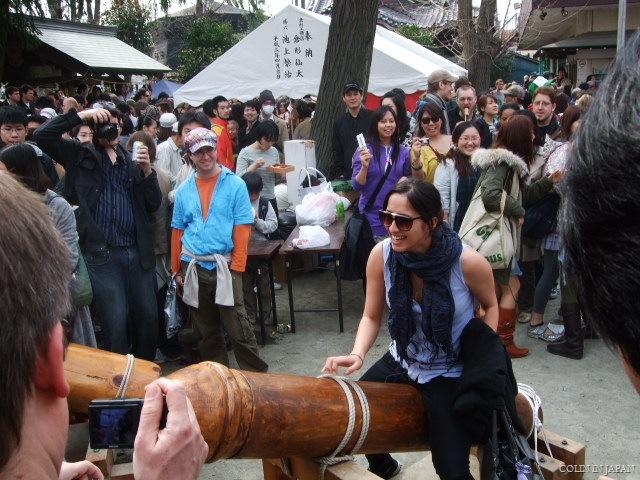 A woman straddles wooden phallus during the kanamara festival, better stock photo